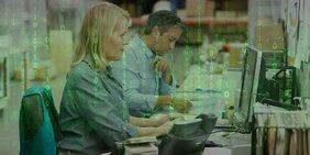 Mann und Frau in Lagerhalle an Computern, darüber (halbtransparent) ein hellgrüner Zahlencode