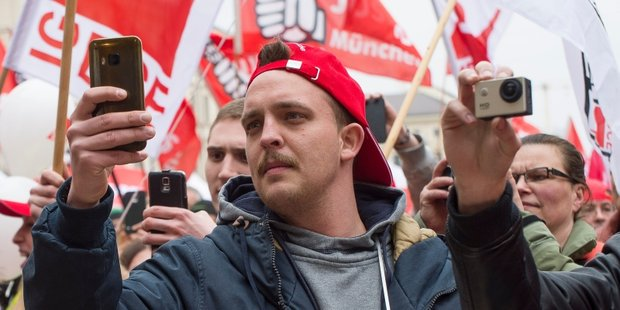 Gewerkschafter mit Handy Smartphone in der Menge macht ein Bild