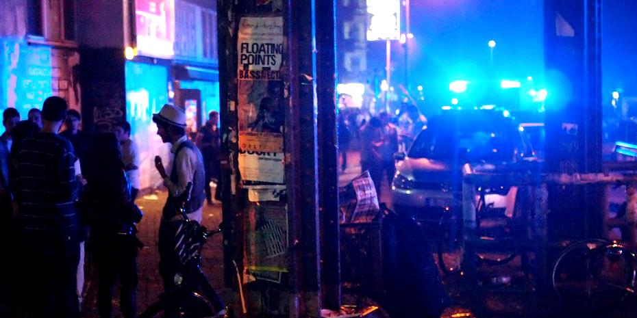 """Polizeiauto mit Blaulicht in nächtlicher Straßenszene mit """"Partygästen"""""""