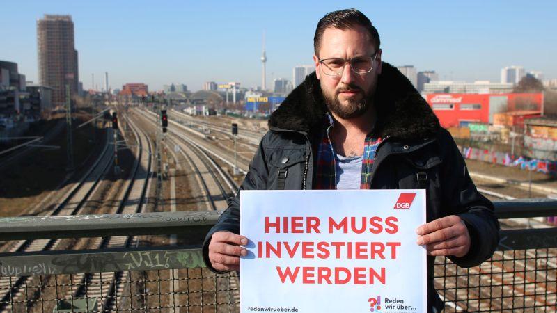 """Reiner Hoffmann mit """"Investier-Hier""""-Schild in Siemensstadt in Berlin"""