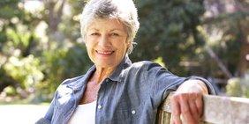 Ältere Frau sitzt lächelnd auf einer Parkbank