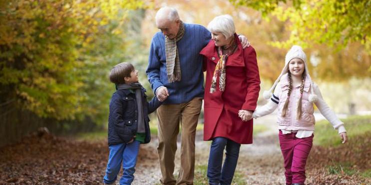 Großeltern spazieren mit Enkelkindern im Wald im Herbst