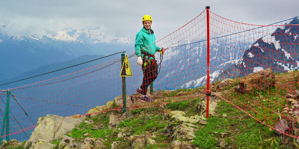 Mann mit Helm und Sicherungsseil in den Bergen