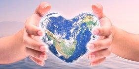 Erde in Herzform in zwei Händen gehalten