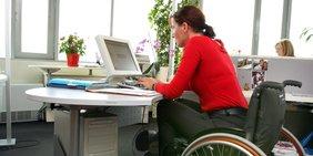 Frau im Rollstuhl sitzt Schreibtisch