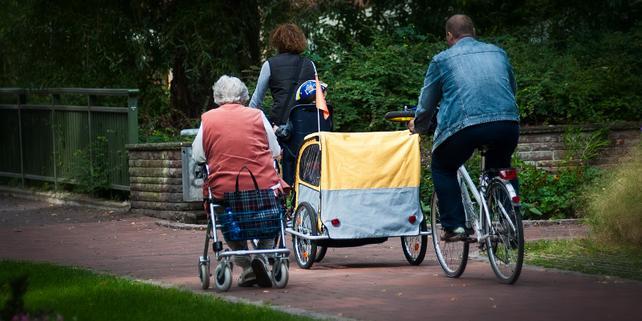 Ältere Frau, Rentnerin, sitzt auf Gehhilfe, Familie mit Fahrrädern und Anhänger