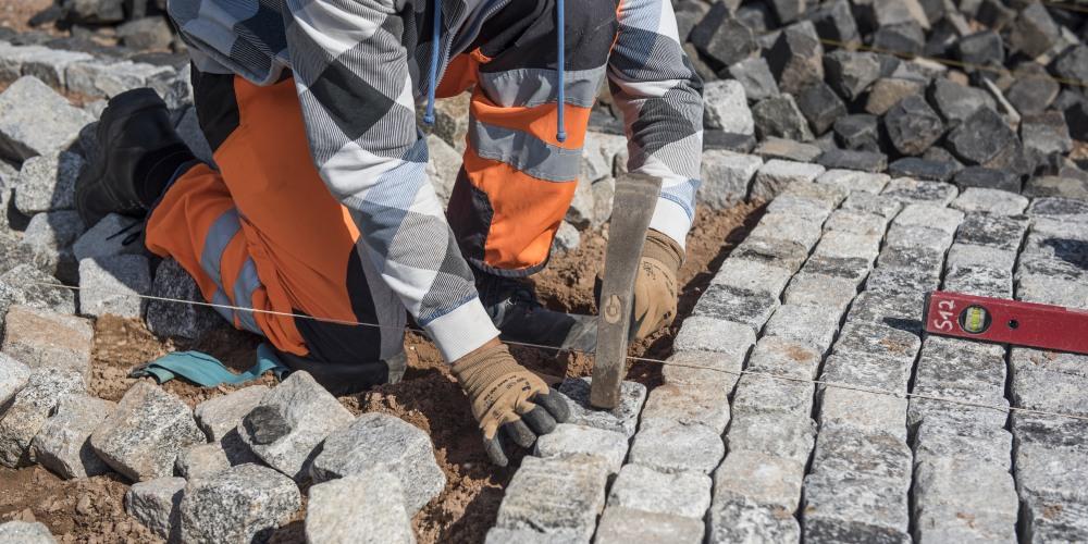 Pflasterer verlegt Granitpflaster