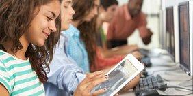 Im Vordergrund: Lächelndes Mädchen mit Tablet; im Hintergrund: Weitere Schülerinnen und Schüler sowie ein Lehrer an Computer-Bildschirmen