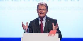 DGB-Vorsitzender Reiner Hoffmann bei Rede an einem Rednerpult mit DGB-Logo
