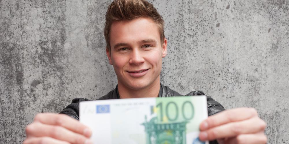 Junger Mann hält einen 100-Euro-Schein in die Kamera
