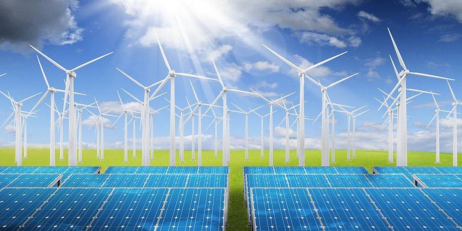 Windräder und Solarpaneele vor grüner Wiese und bewölktem Himmel