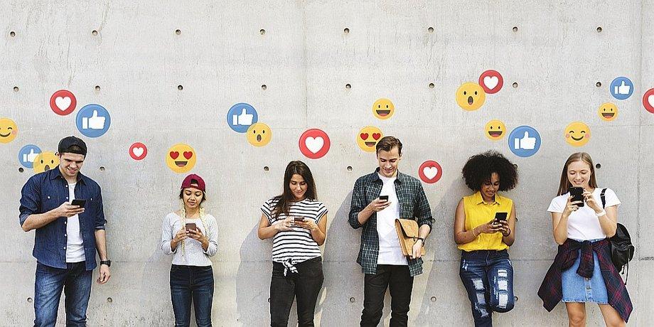 Junge Menschen mit Smartphones umringt von Emoji Symbolen