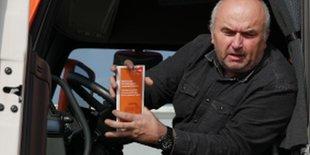 LKW Fahrer mit Fair Posting Flyer in der Hand