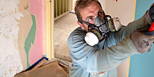 Handwerker mit Schutzmaske bei Abrissarbeiten in Wohngebäude