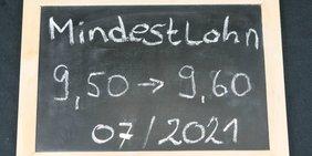 Kreidetafel mit Kreideschrift zur Mindestlohnerhöhungsbeträgen im Juli 2021 von 9,50 Euro auf 9,60