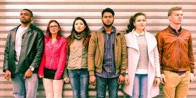 Gruppe junger Menschen unterschiedlicher Herkunft steht vor einem Rolltor