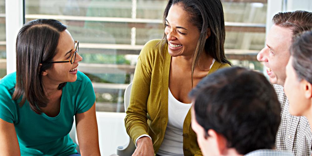 Gruppe von Menschen sitzt im Kreis, diskutiert, lacht