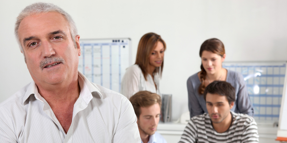 Älterer Mitarbeiter in einem Büro im Vordergrund, dahinter Gruppe jüngerer Mitarbeiter