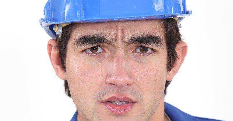 junger mann mit Bauhelm und Blaumann, Nahaufnahme Gesicht, blickt skeptisch