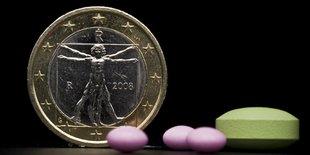 Ein 1 Euro Stück und rosane und grüne Tabletten davor.