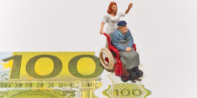 Modellfigur Frau mit Rollstuhlfahrer auf 100-Euro-Schein