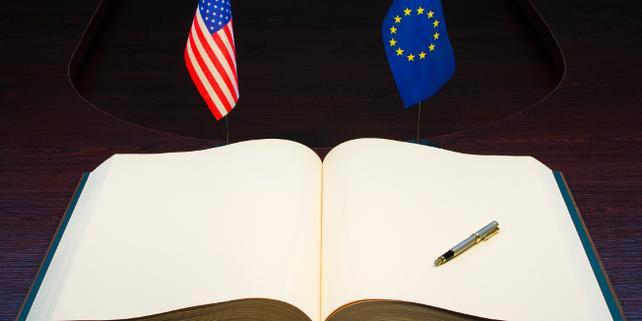 Fahnen USA, EU auf Tisch mit Buch zur Unterschrift