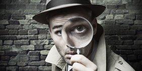 Detektiv schaut durch eine Lupe, schwarz-weiß