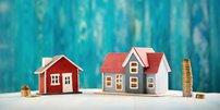Kleines und großes Haus jeweils mit kleinem und großem Münzstapel