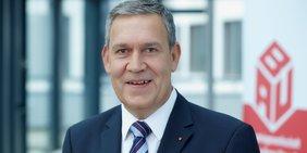 Portrait des IG-BAU-Vorsitzenden Robert Feiger; Hintergrund: Logo der IG BAU