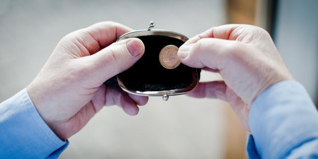 Hand greift nach Cent (Euro) in Geldbörse / Geldbeutel