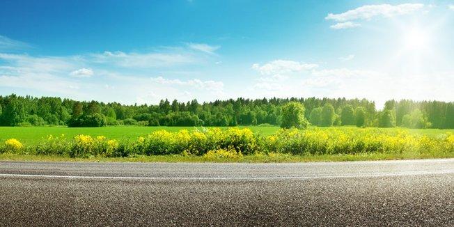 Straße mit grüner Landschaft bei wolkigem Himmel