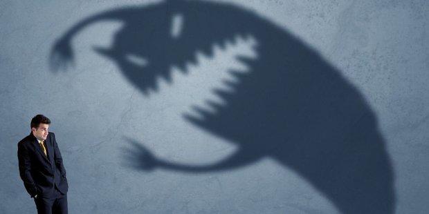 Geschäftsmann geht vor vermeintlich übermächtigem Schattenmonster in Deckung