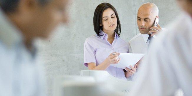 Frau und Mann mit Handy am Ohr schauen gemeinsam auf ein Blatt