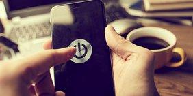 Menschliche Hand will Smartphone ausschalten