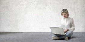 Frau mit Laptop sitzt auf dem Boden