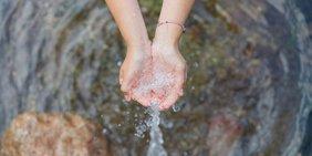 Hände fangen Wasserstrahl auf