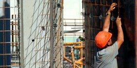 Bauarbeiter mit orangefarbenem Bauhelm  befestigt ein Gitter auf einer Baustelle