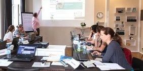 Menschen in einem Weiterbildungsseminar; im Hintergrund zeigt der Seminarleiter auf eine Leinwand mit Präsentation