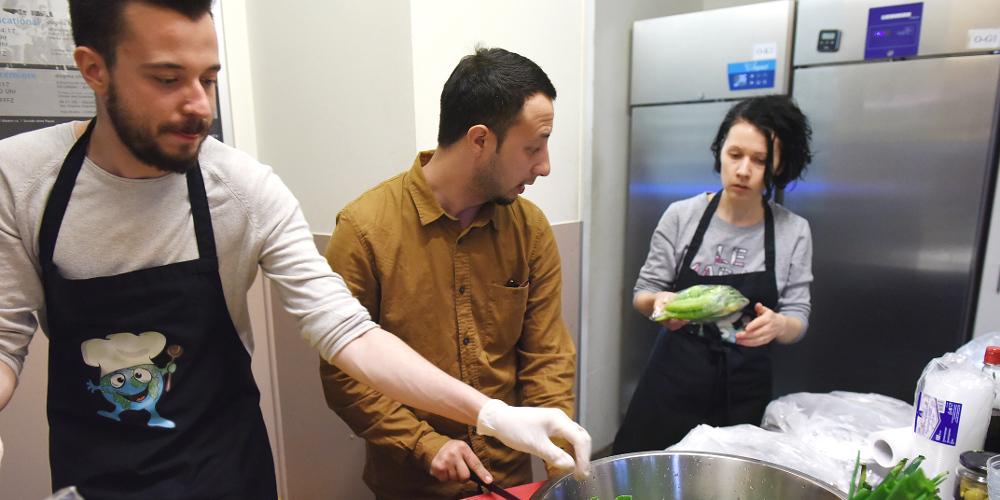 Zwei Männer und eine Frau kochen gemeinsam