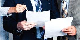 Drei Personen mit Papieren in den Händen