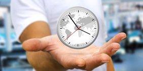 Uhr schwebt über ausgestreckter männlicher Hand
