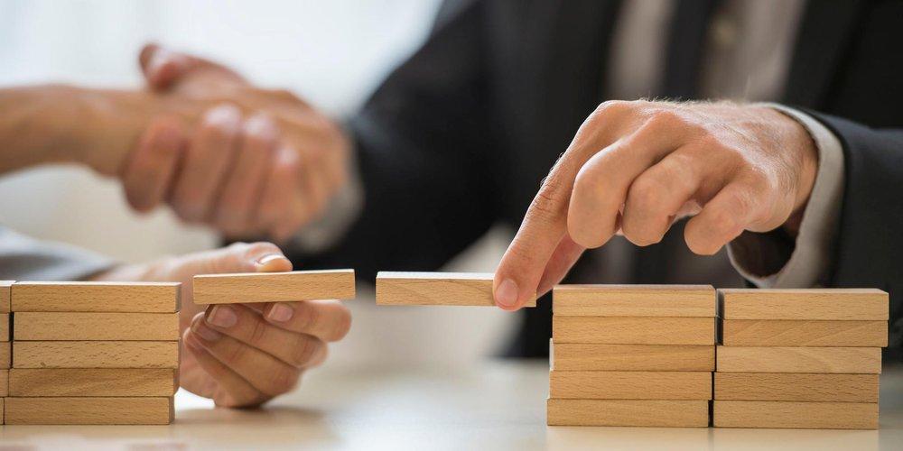 Hände halten Holzbausteine, die eine Brücke über einen Spalt bilden