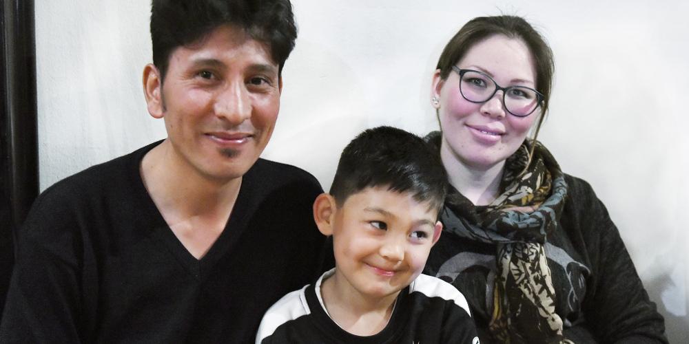 Familie (Mutter, Vater, Sohn) blickt lächelnd in die Kamera