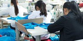Asiatische Frauen arbeiten an Nähmaschinen in Textilfabrik