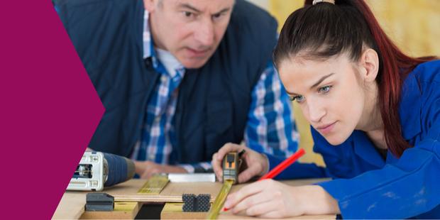 Azubi (junge Frau) mit Maßband an Holz-Werkstatt; im Hintergrund der Ausbilder