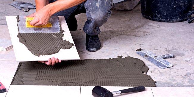 Nahaufnahme der Hände eines Fliesenlegers mit Fliese und Werkzeug