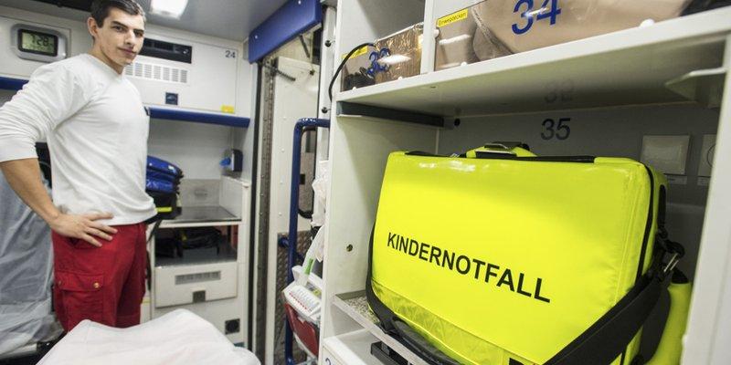"""Rettungssanitäter im Inneren eines Krankenwagens; im Vordergrund ein neon-gelber Koffer mit der schwarzen Aufschrift """"Kindernotfall"""""""