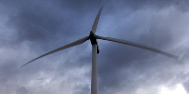 Ein Windrad unter stark bewöltem Himmel