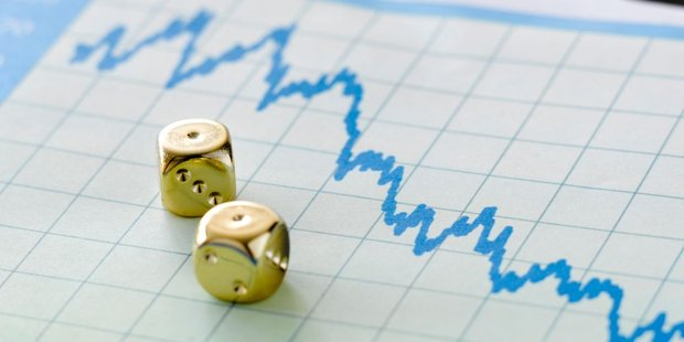 Zwei goldene Würfe liegen auf einem Papier mit der Abbildung eines im Sinkflug befindlichen Börsenkurses