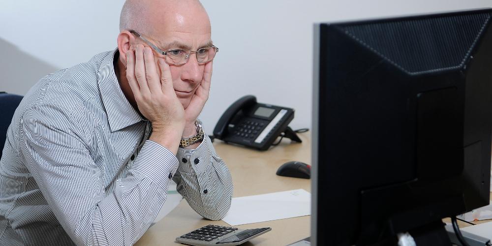 Mann, Kopf auf Hände gestützt, vor PC